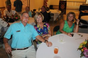 A group of people sitting at a table posing for the camera - Mike Dunn