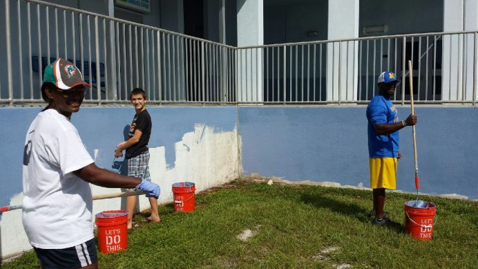 Students tackle some painting near the middle school and auditorium entrance.
