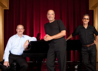 Gordon Ross and friends coming to theater - A person standing in front of a red curtain - Public Relations