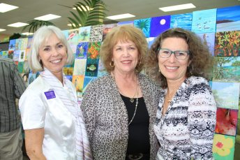 "Florida Keys Council of the Arts Vice Chair Lucy Carleton, left, Chair Theresa Axford, and Executive Director Liz Young at the event reception at Royal Furniture on Thursday. ""The mosaic is our signature project to promote the visual arts within the community,"" Young said."