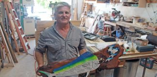 Artist focuses on the splendor of local wood - A man sitting on a table - Artisan
