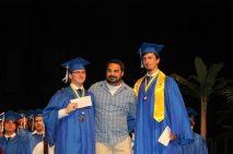 Grads receive awards – Scholarships further seniors' education goals - A man holding a blue umbrella - Graduation ceremony