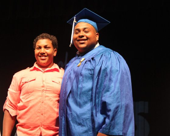 Freshman Jordy Mejia, left, caps his older brother, 'Meja,' at the ceremony.