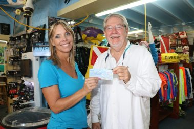 Tilden's owner Wendy Hall hands Sanctuary Friends Board President George Neugent a check for $5,300 raised during from the tournament.