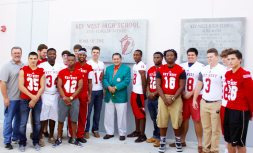 George Mira, Key West High alumni and former Miami Dolphin, stands proudly with varsity football team, Fighting Conchs.
