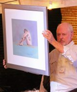Reef Perkins helps show off pieces of art. Here, he holds 'Women on Green' by local life artist Annamarie Giordano.