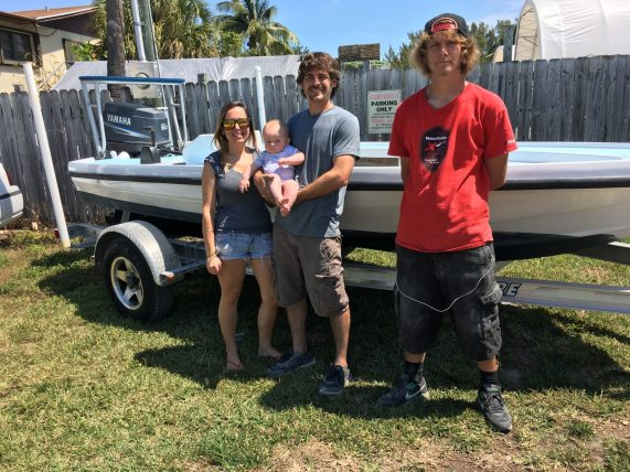 "Frank with his wife Shawna and six-month-old son Tristan and employee Corey Bibb, right, stand with a repainted flats boat owned by John Ryan. ""He is a man of his craft,"" said Ryan. ""He takes true pride in what he does."""