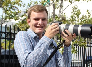 Teen photog is 'Workin' for a Livin'' - A man standing in front of a fence - Photography