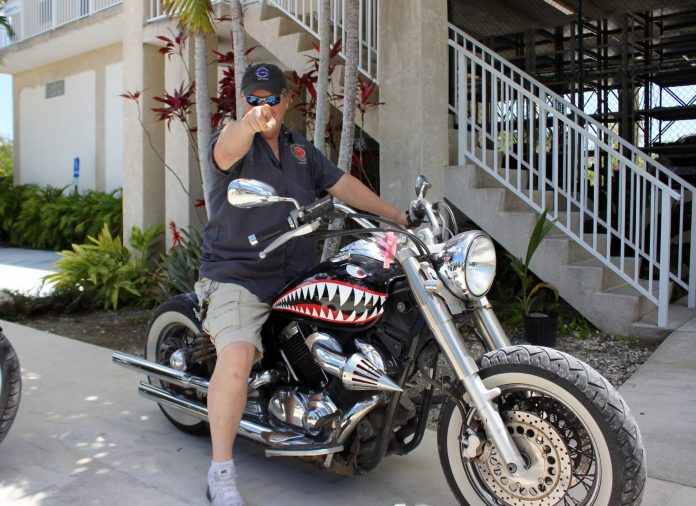 20 questions with Bill Hoebee - A man riding a motorcycle on the side of a building - Car tires