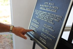 Former manager Mike Puto points to the name of the late Mayor Dick Ramsay on the special dedication plaque.