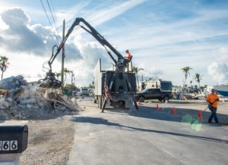 Hurricane land debris collection nearing completion - A person riding on the back of a truck - Road