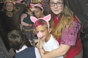 Sara Gonzales (Pinocchio) and Jack Dunn (a pig from Three Little Pigs) huddle backstage during a recent rehearsal.