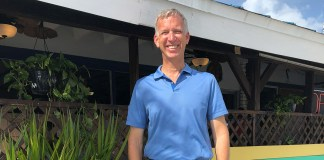 """Charles """"Chuck"""" Licis works  tirelessly for Take Stock - A man in a blue shirt standing in front of a building - Florida Keys"""