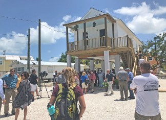 Ribbon cut on first 'Maggie House' - A group of people standing outside of a building - Florida Keys