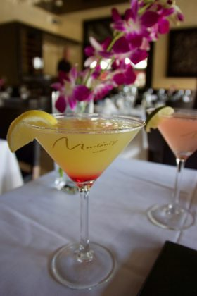 The Happiest of Hours: Martin's is a Key West Favorite - A glass of wine sitting on top of a table - Cocktail garnish