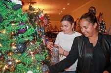 """Maylin Ibarra, left, and Yessenia Crespo sprinkle tinsel on the IOA Insurance Agency tree. It has a clever """"Nightmare before Christmas"""" theme."""