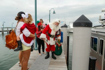Santa gets some help removing a life jacket after a boat ride from Coast Guard Station Islamorada via a Coast Guard cutter to Bass Pro Shop's World Wide Sportsman in Islamorada. Kids and adults came out to meet Santa and have their picture taken with him aboard Hemingway's boat Pilar.