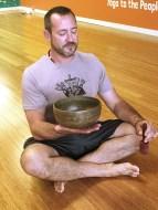 Key Largo Yoga instructor Damian Groak in a meditative pose with a sound bowl. ELLEN T. WHITE/Keys Weekly