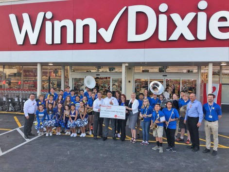 Winn-Dixie re-opens in Marathon - A group of people standing in front of a sign - Winn-Dixie