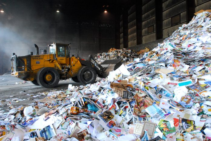 Recycling rates are increasing, but so is 'contamination' - A construction vehicle next to a truck - Recycling