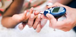 Our Barefoot Doctor considers how Diabetes affects Kids - A close up of a hand holding a cell phone - Type 1 diabetes