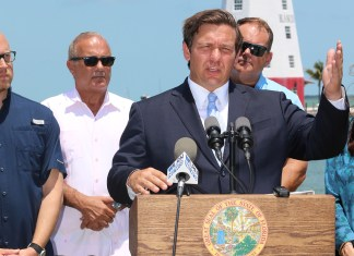 Governor makes first official visit to the Keys - A group of people standing next to a man in a suit and tie - Ron DeSantis