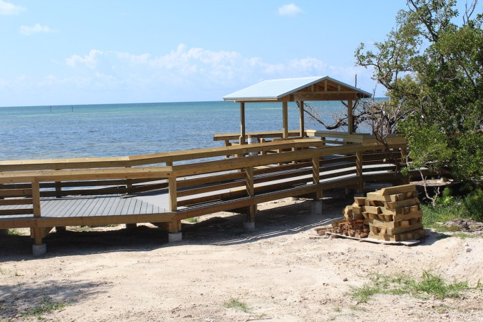 Welcome the Long Weekend at the Beach! Anne's Beach Offers New Boardwalk - A wooden bench sitting on top of a sandy beach - Anne's Beach