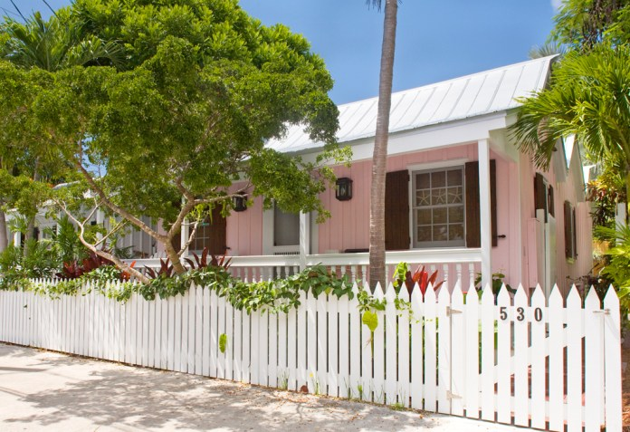 Welcome Home! Key West Families move in via Homebuyer Assistance Program - A close up of a white fence in front of a house - Our Key West Local Concierge, Welcome Lounge & Galleria - OKW