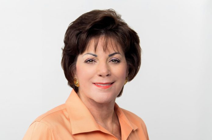 Virginia Panico Announces Retirement – Key West Chamber Head Steps Down in December - A woman wearing a white shirt and smiling at the camera - Florida Keys