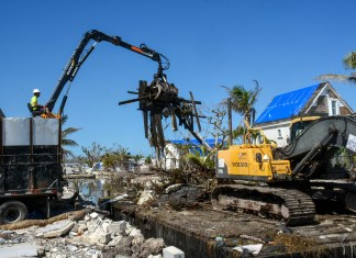 County: 76 more canals to be cleaned in the Keys - A crane next to a pile of dirt - Florida Keys