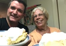 Key Lime Legends – The Cookie Lady - A person is smiling while holding a piece of cake on a plate - Florida Keys