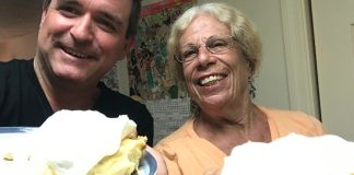 Key Lime Legends –The Cookie Lady - A person is smiling while holding a piece of cake on a plate - Florida Keys