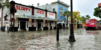 What FEMA flood maps mean for residents, real estate - A group of people walking down a street next to water - Sloppy Joe's Bar