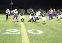 Canes Convincing In First Win Of Season - A group of people playing football on a field - American Football