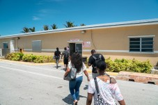 Keys Weekly photographer documents Bahamas plight - A group of people walking in front of a building - Florida Keys