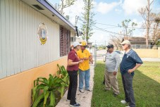 Keys Weekly photographer documents Bahamas plight - A group of people standing in front of a house - Florida Keys