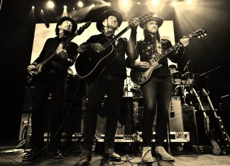 Allman Betts Band Plants New Roots - A group of people standing on a stage posing for the camera -