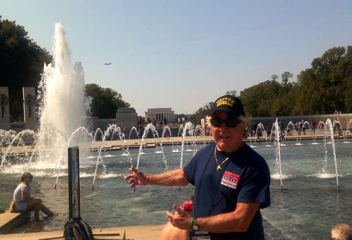 Capt. Skip tours nation's capital with fellow vets - A man standing next to a fountain - Water