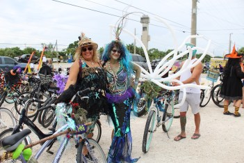 BROOMSTICK PARKING ONLY –AnnualWitches'Ride raises funds for cancer research - A group of people standing next to a bicycle - Road bicycle