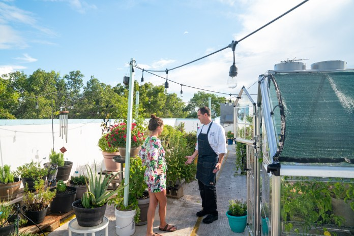 CATCH AND DINE – Program shows mindful harvesting, food preparation - A man and a woman standing in front of a building - Greenhouse
