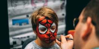 GROWN-UP PARTY GIVES WAY TO YOUNGER CROWD – KIDS COUNT DOWN TO TRICK-OR-TREATING - A close up of a person talking on a cell phone - Painting