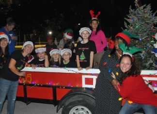 'CARING AND SHARING AROUND THE WORLD' – Hammon grand marshal of Islamorada Holiday Parade - A group of people riding on the back of a truck - Fête