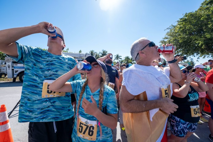 RUNNING THE ISLANDS - A group of people are drinking from a bottle - Marathon