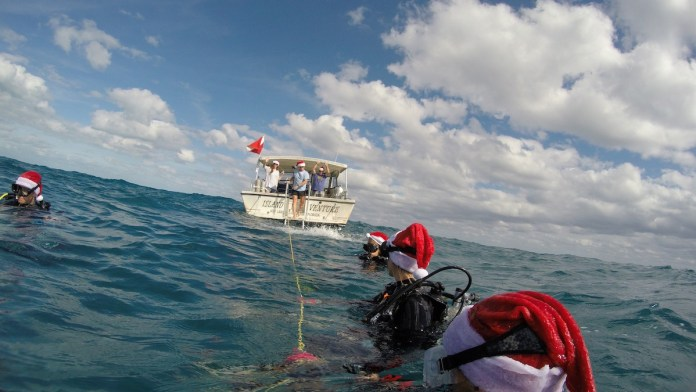 WINNER – Keys Holiday Photo Contest - A man riding on the back of a boat in a body of water - Florida Keys