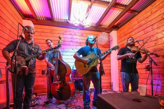 Eighth annual Baygrass Bluegrass set - A group of people standing on a stage holding a guitar - Uproot Hootenanny