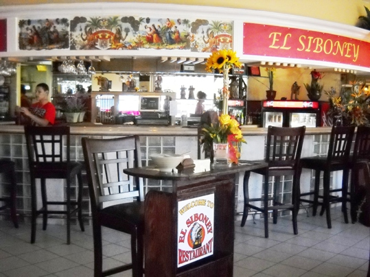 Starkly different from its former inhabitants, the restaurant space at Gulfside Village is now decorated with warm red and yellow hues as well as vibrant images of Cuba