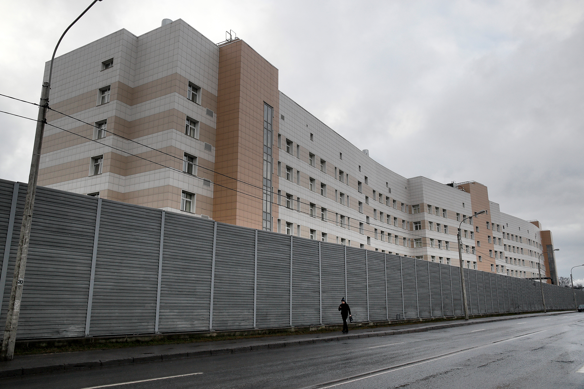 A man walks past a fence in front of the Botkin hospital in St. Petersburg, Russia, Wednesday, Feb. 12, 2020. A patient has fled the hospital where she was quarantined after coming down with a sore throat after returning to St. Petersburg from Hainan in China. (AP Photo/Dmitri Lovetsky)