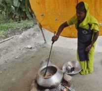 A cook prepares food for free mid-day meal for children, distributed by government-run primary school, at Brahimpur village