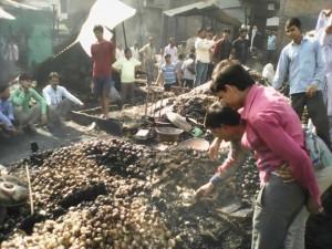 घटना के दूसरे दिन खाक हुई सब्जियों के ढेर के बीच लोग