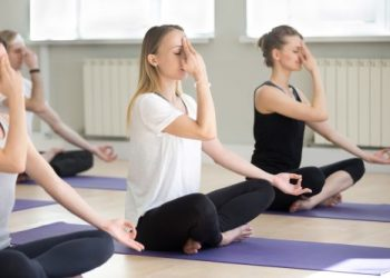 Group of young sporty people practicing yoga lesson in gym, doing Alternate Nostril Breathing exercise, nadi shodhana pranayama pose, working out, indoor, students training in sport club, studio